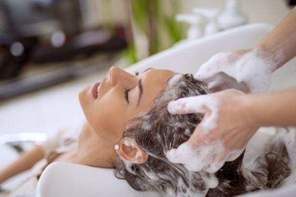 champu-sin-sulfatos-ventajas-e-inconvenientes-a-mujer-le-lavan-la-cabeza-istock